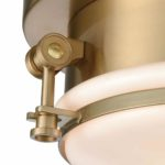 the Riley flush mount unites metal and glass with die cast brackets and nautical thumbscrews. A cast socket housing and canopy further add to its industrial character. Finished in Satin Brass with opal white glass.