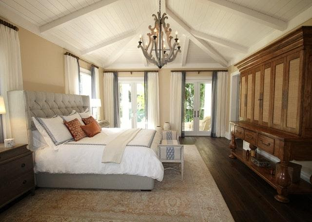 A bedroom with a big bed and a luxurious chandelier.